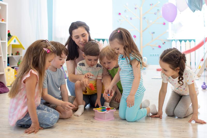 Female teacher teaching kids play toy in class room. Kindergarten preschool concept stock image