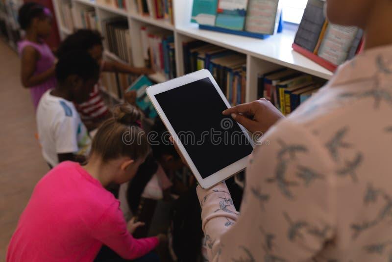 Female teacher working on digital tablet in school library stock photo