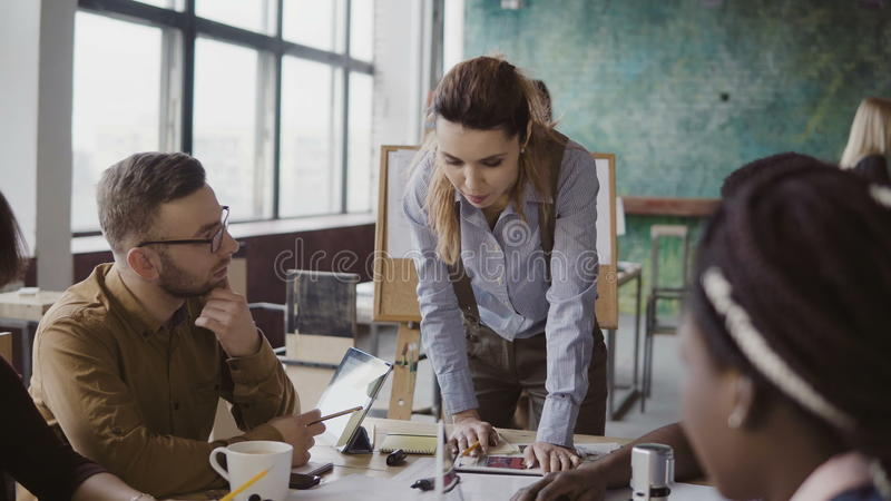 Female team leader standing near table and giving direction to young creative team. Brainstorming of multiethnic group. stock photo