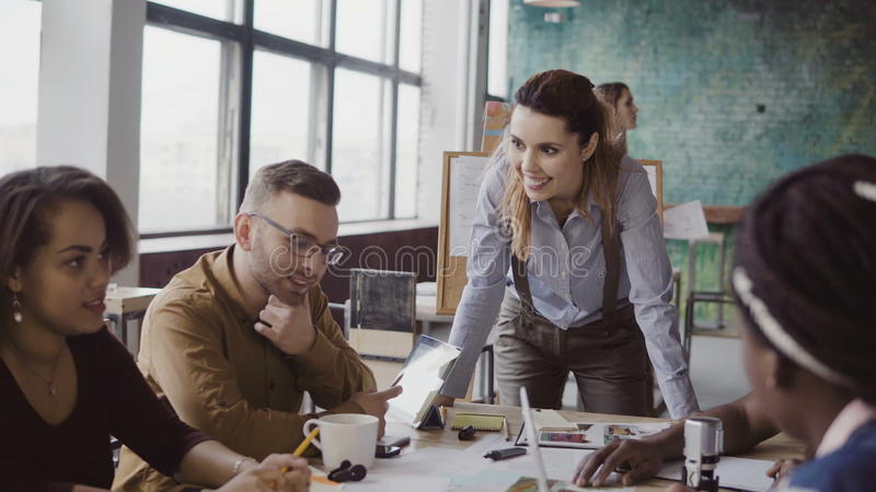 Female team leader standing near table and giving direction to young creative team. Brainstorming of multiethnic group. royalty free stock photography