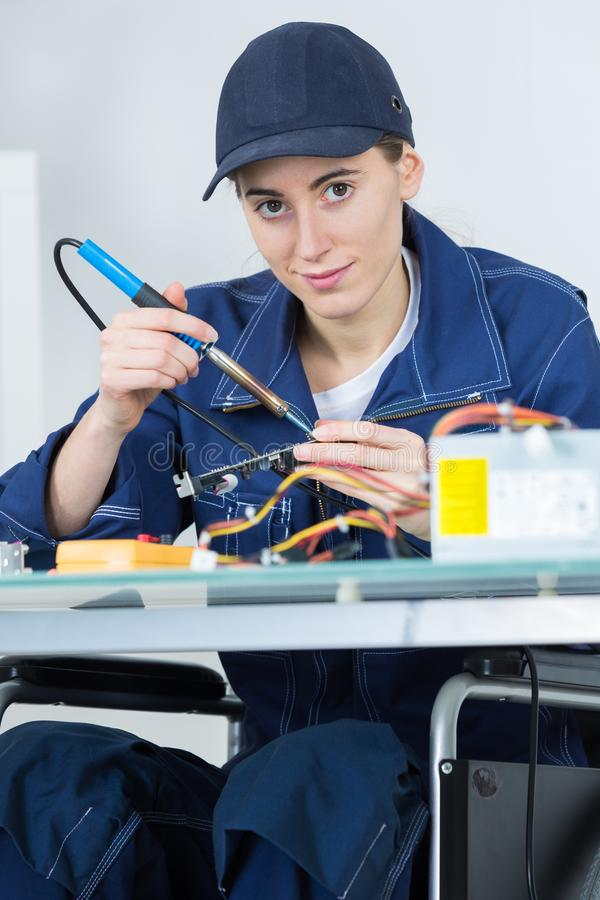 Female technican soldering electronic printed board stock photography