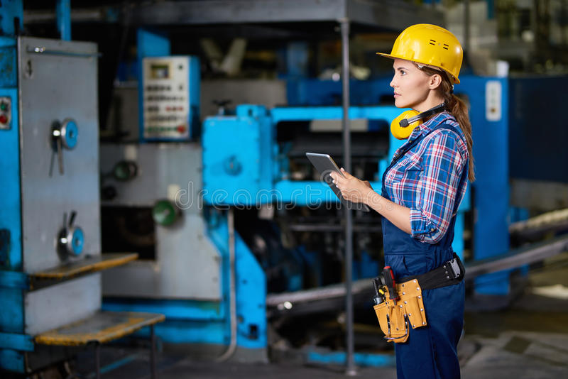 Female Technician Checking Machines at Factory royalty free stock photography