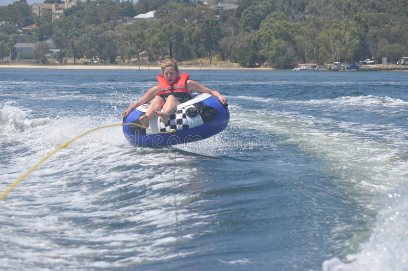 Female teen girl tubing on the river royalty free stock photo