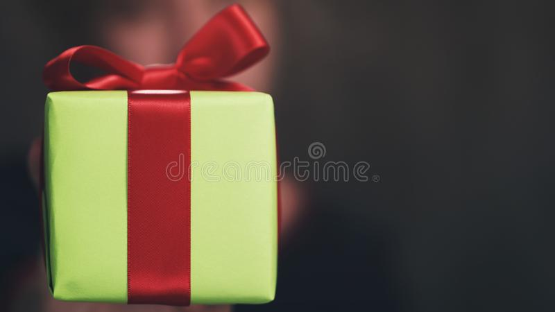 Female teen hand show green paper gift box with red bow stock photography