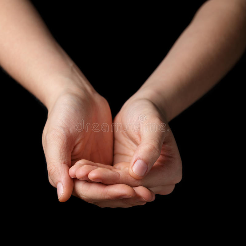 Female teen hands begging for something. Isolated on black stock photos