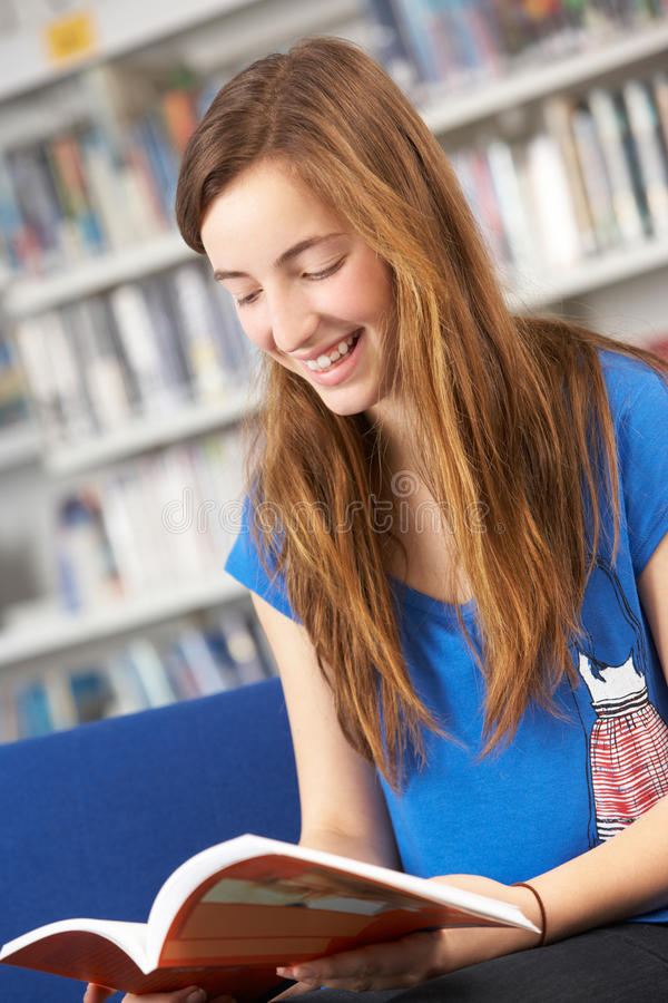 Female Teenage Student In Library Reading Book. Smiling royalty free stock image