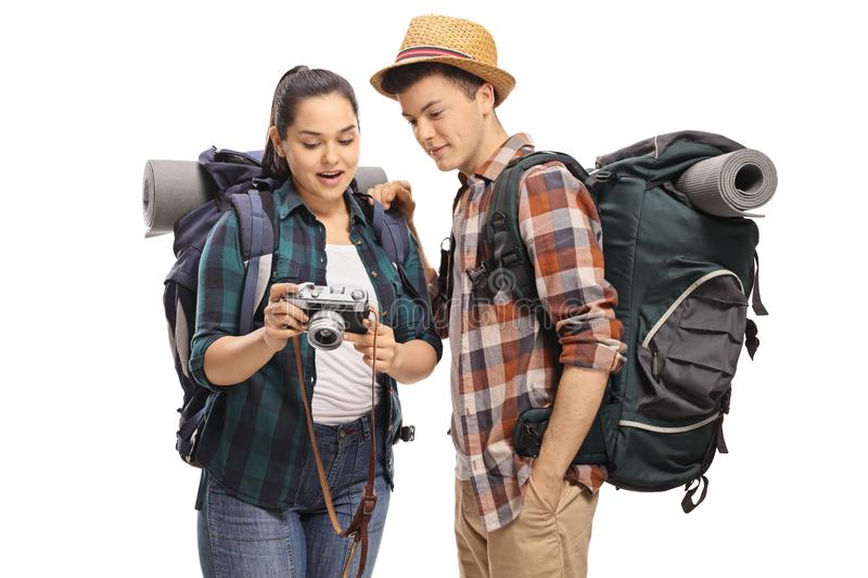 Female teenage tourist showing pictures on a camera to a male to. Urist isolated on white background royalty free stock images