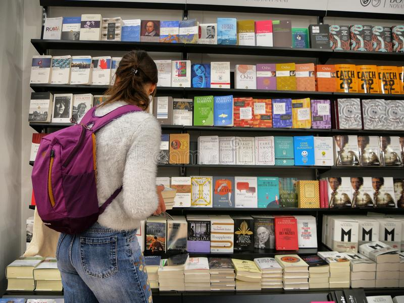 Female teenager choosing a book in colorful bookstore stock photos