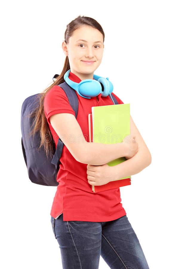 Female teenager with schoolbag and headphones holding notebooks stock photography