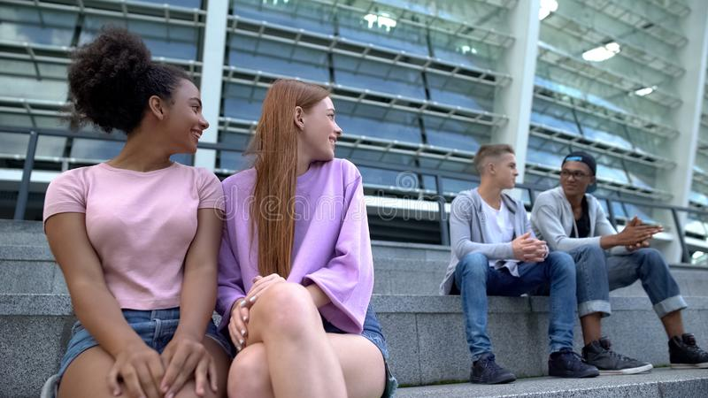 Female teenagers looking at male students sitting stairs, first relations, flirt. Stock photo stock image