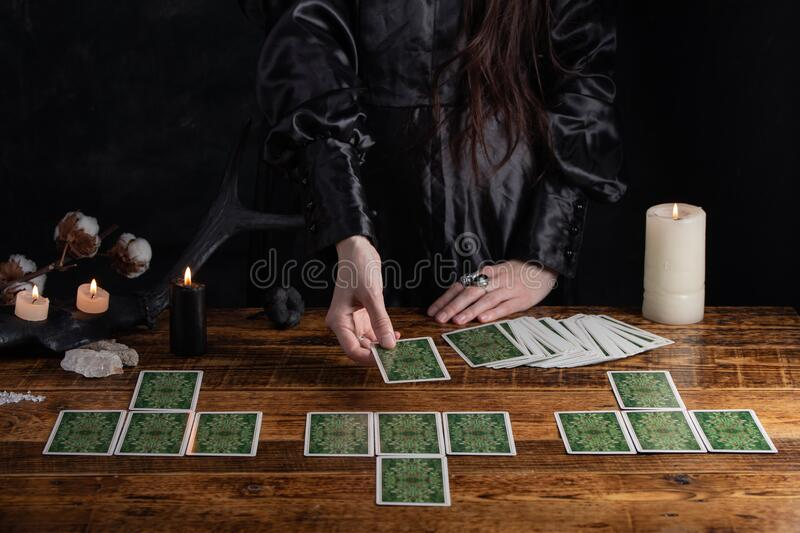 Female tells the future with playing cards. Tarot card concept on the table. Prediction of the future. Fortuneteller hands in. Black vestments stock photography