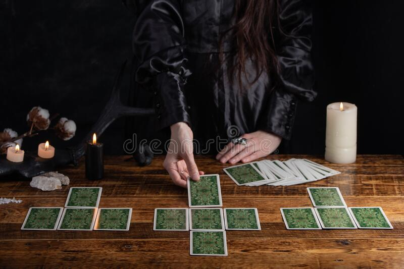 Female tells the future with playing cards. Tarot card concept on the table. Prediction of the future. Fortuneteller hands in. Black vestments stock photos