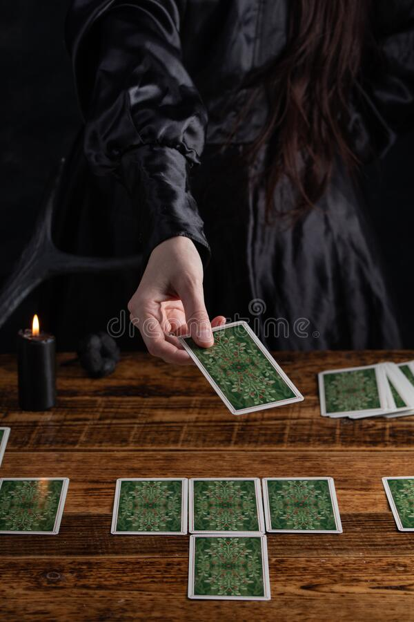 Female tells the future with playing cards. Tarot card concept on the table. Prediction of the future. Fortuneteller hands in. Black vestments royalty free stock photos