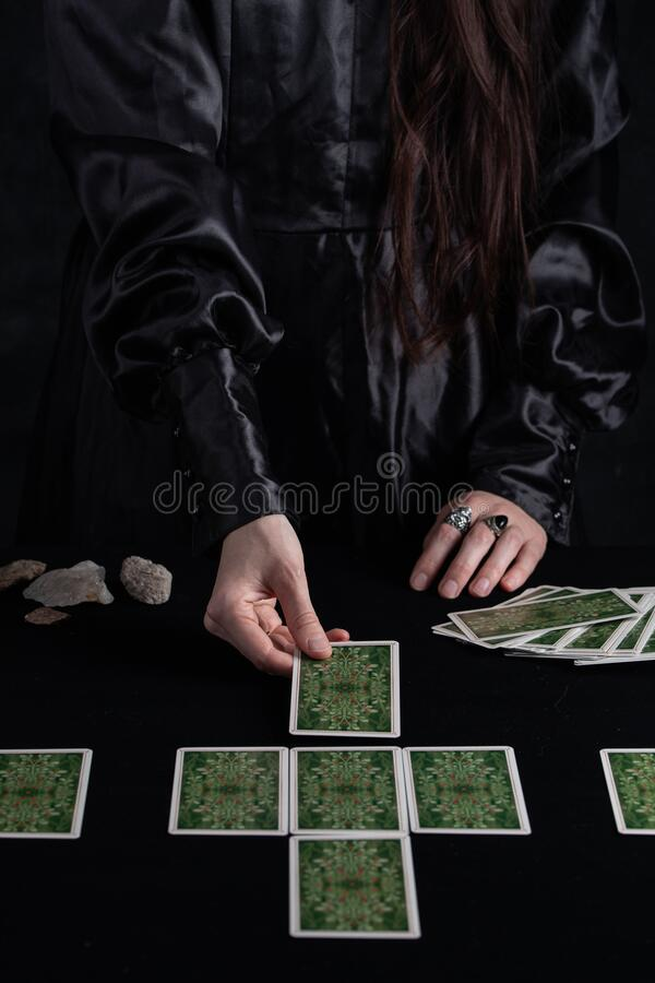 Female tells the future with playing cards. Tarot card concept on the table. Prediction of the future. Fortuneteller hands in. Black vestments royalty free stock photography
