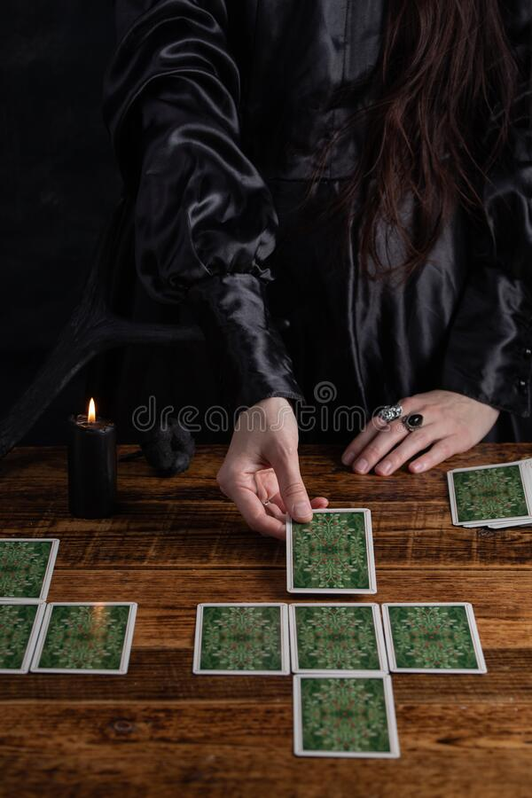Female tells the future with playing cards. Tarot card concept on the table. Prediction of the future. Fortuneteller hands in. Black vestments royalty free stock image