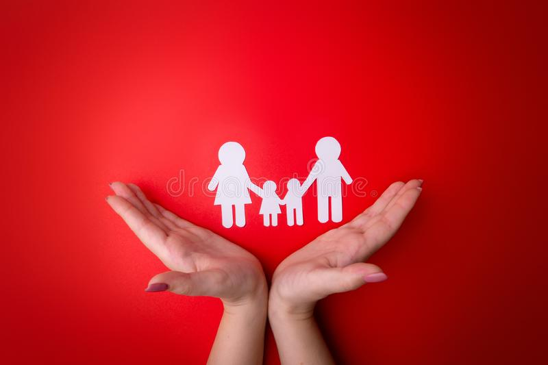 Female tender hands with a family symbol cut out of white paper. Protecting the rights of people and sexual minorities. Love for stock image