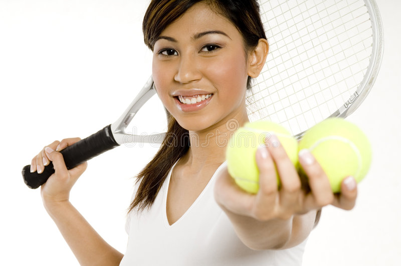 Female Tennis Player. A young Asian woman holding a tennis racket and holding two yellow tennis balls (shallow depth of field used and focus on woman royalty free stock photos