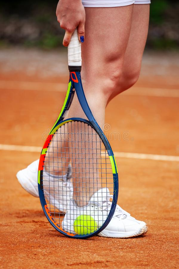 Female tennis player legs in tennis shoes standing on a clay court stock photo