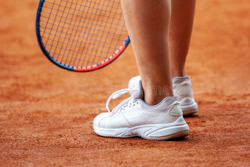 Female tennis player legs in tennis shoes standing on a clay court royalty free stock images