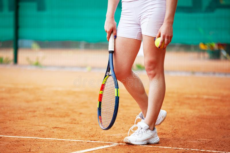 Female tennis player legs in tennis shoes standing on a clay court royalty free stock photos