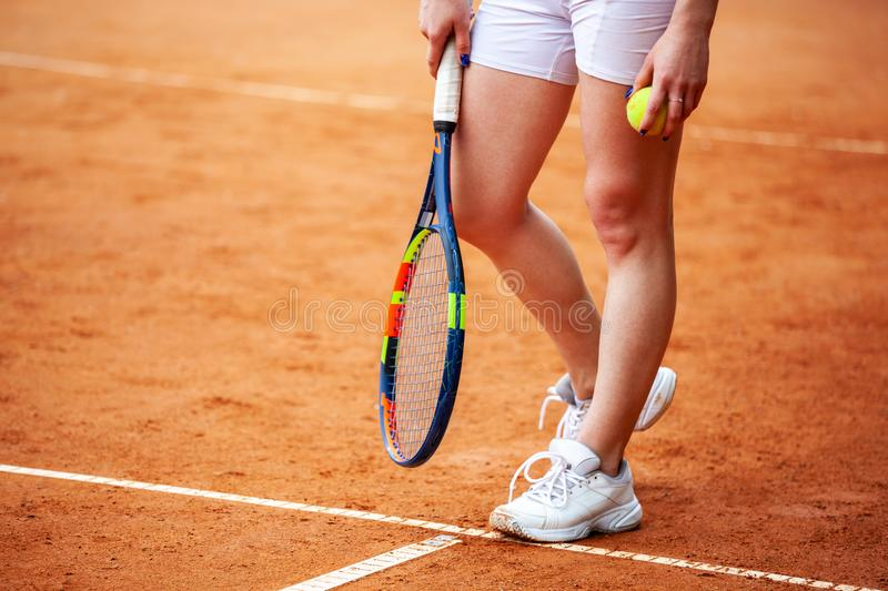 Female tennis player legs in tennis shoes standing on a clay court royalty free stock photography