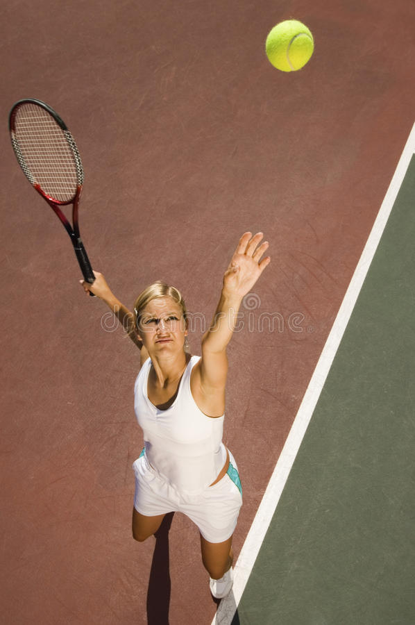 Female Tennis Player Serving Ball On Court stock images
