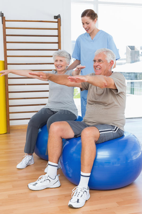 Female therapist assisting senior couple with exercises royalty free stock photography