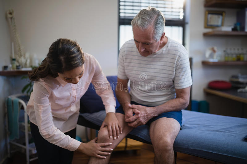 Female therapist examining knee of senior male patient stock photo