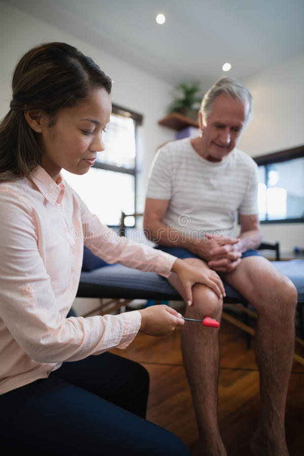 Female therapist examining knee of senior male patient with reflex hammer royalty free stock photos