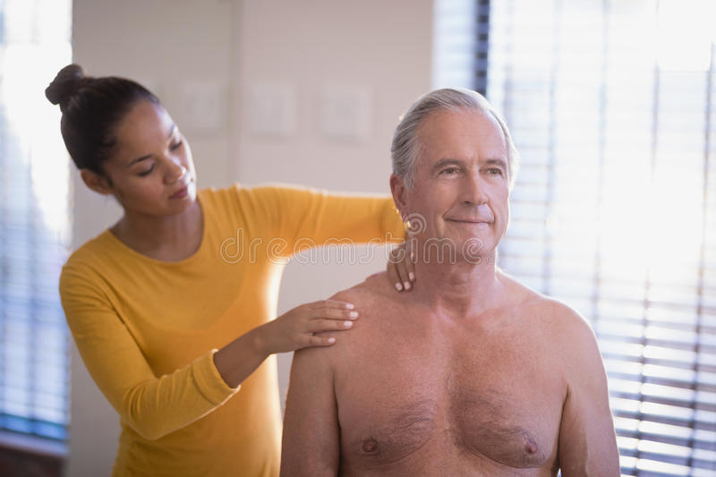 Female therapist giving neck massage to shirtless senior male patient. At hospital ward royalty free stock image