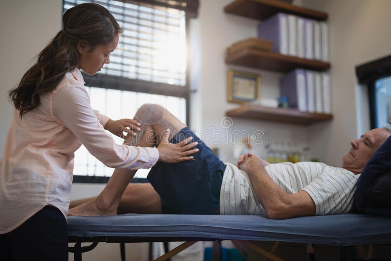 Female therapist measuring knee while senior male patient lying on bed royalty free stock photography