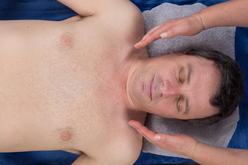 Female therapist performing Reiki over face of man at health spa stock photography