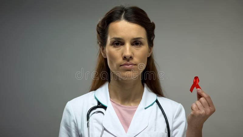 Female therapist showing red ribbon before camera, safe sex, AIDS prevention royalty free stock photo