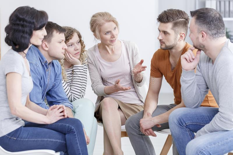 Therapist talking to patients. Female therapist talking to her patients during a support meeting stock photo