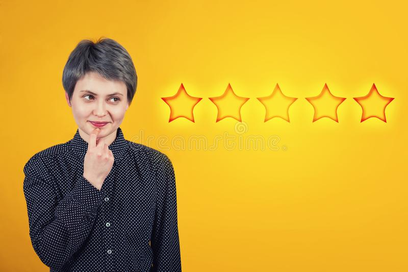 Female thinks of choosing five stars rating, positive feedback. Excellent customer service concept. Satisfied client voting survey. Dreamy woman hipster royalty free stock images