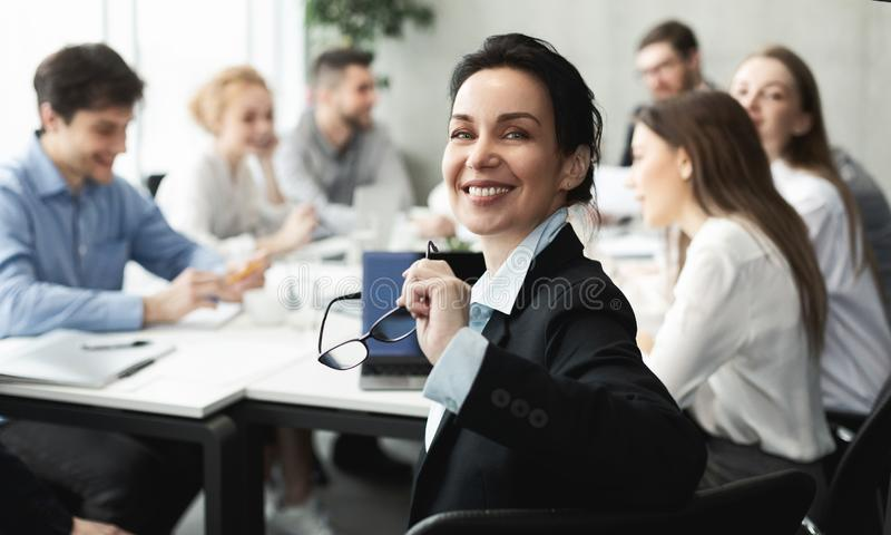 Female top manager smiling to camera at meeting stock photo