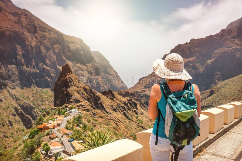 Female tourist with backpack admires view of Masca village. Back view of female tourist with backpack admires view of Masca village royalty free stock images
