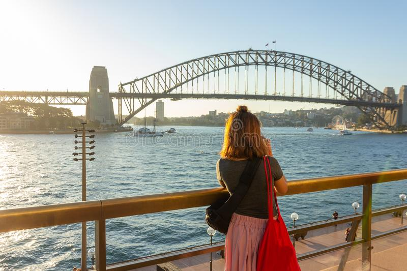 Female tourist with backpack bag taking photos of Sydney Harbour Bridge royalty free stock photography