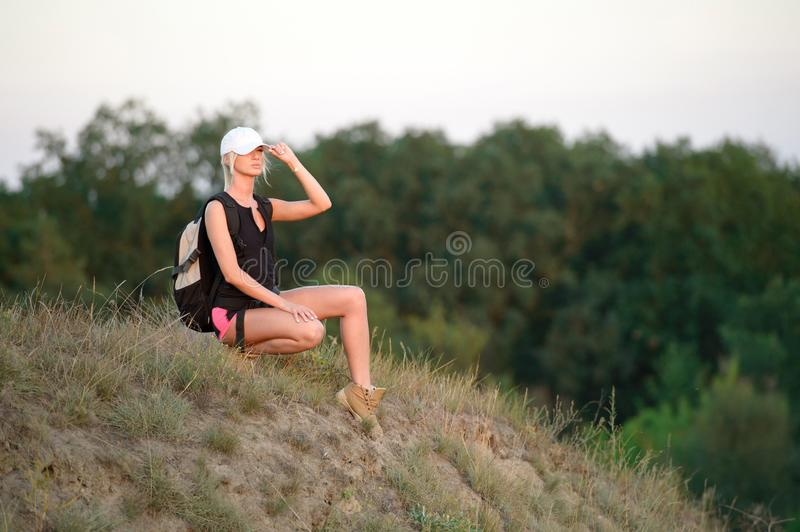 Female tourist with backpack enjoying beautiful forest view. The Female tourist with backpack enjoying beautiful forest view royalty free stock image