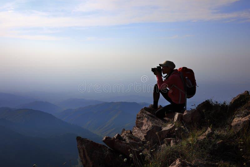 Female tourist taking photo on mountain peak stock photo