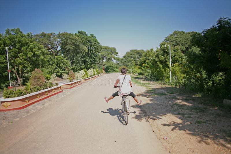 Woman cycling between Bagan temples royalty free stock photography