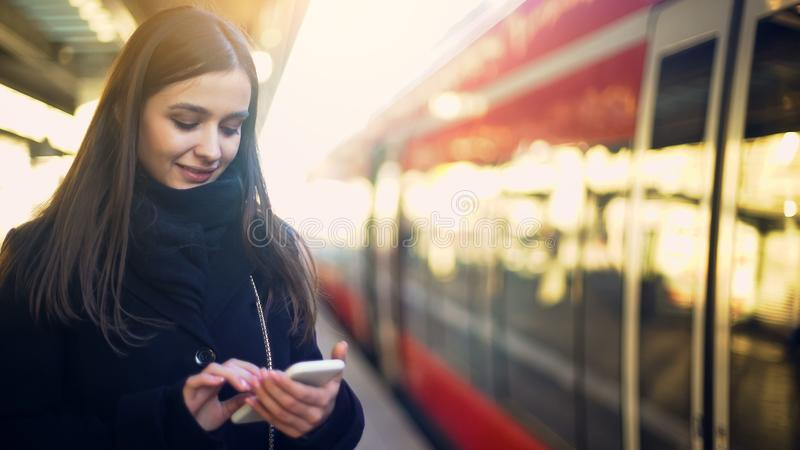 Female tourist booking sightseeing tour on smartphone, standing in train station royalty free stock image