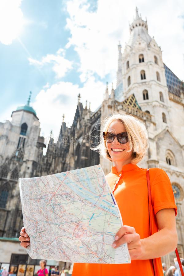 Female tourist stands on Stefansplatz in Vienna near St. Stephen`s Cathedral holding a map of the city and withering it royalty free stock image