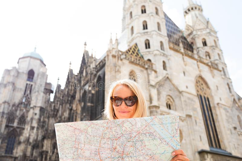 Female tourist stands on Stefansplatz in Vienna near St. Stephen`s Cathedral holding a map of the city and withering it stock images