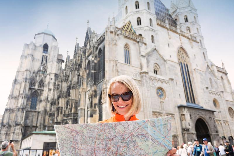 Female tourist stands on Stefansplatz in Vienna near St. Stephen`s Cathedral holding a map of the city and withering it royalty free stock images