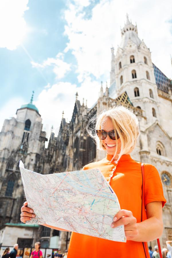 Female tourist stands on Stefansplatz in Vienna near St. Stephen`s Cathedral holding a map of the city and withering it stock photo