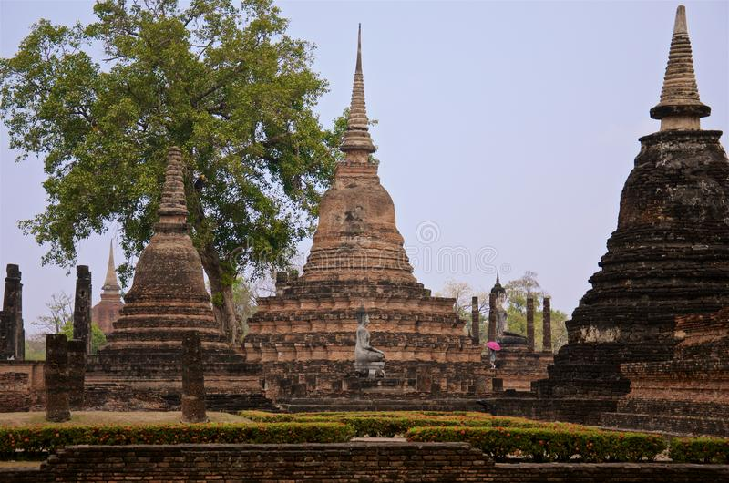 Female tourist with a bright umbrella among pagodas in famous Sukhothai Historical Park stock images