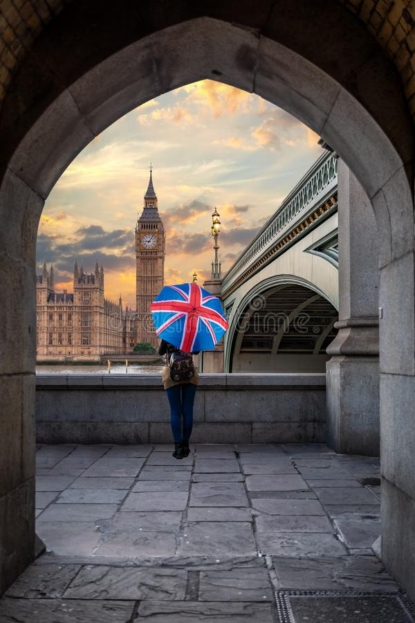Female tourist with a British flag umbrella in front of the Big Ben royalty free stock photo