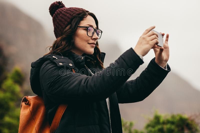 Female tourist capturing the landscape in her phone royalty free stock photography