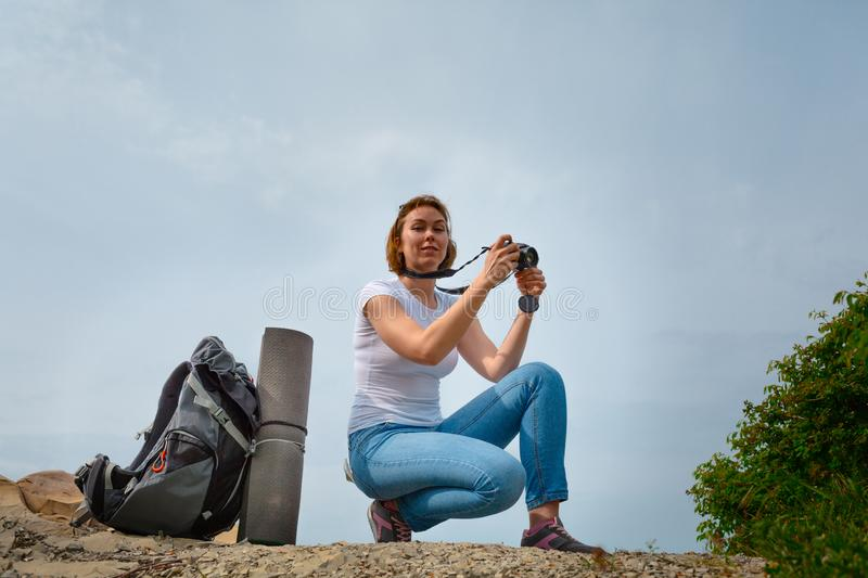 Woman tourist decided to relax and take some memorable photos on the phone. Sky on the background. Female tourist decided to relax and take some memorable photos stock photography